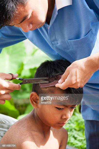 Indian children getting haircuts. Older boy cuts younger child's hair.