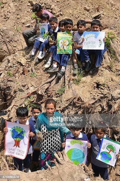 Indian children hold placards near a chopped tree at a demonstration to mark Earth Day in Amritsar on April 22 2015 Earth Day is observed each April...