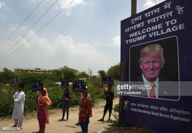Indian children hold placards next to a billboard with the image of US President Donald Trump by the entrance gate of Marora village which has been...
