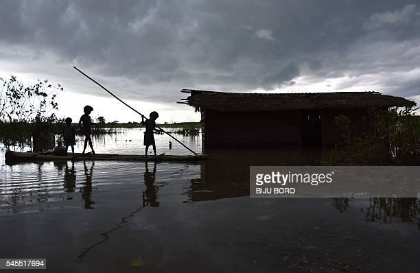 TOPSHOT Indian children paddle a raft near their partially submerged house in the floodaffected Mayong village in the Morigoan district of Assam on...