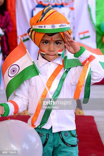 Indian children paint the tricolor of Indian flag on their face and raise the National Flag on the eve of republic day celebrations in Rajasthan India