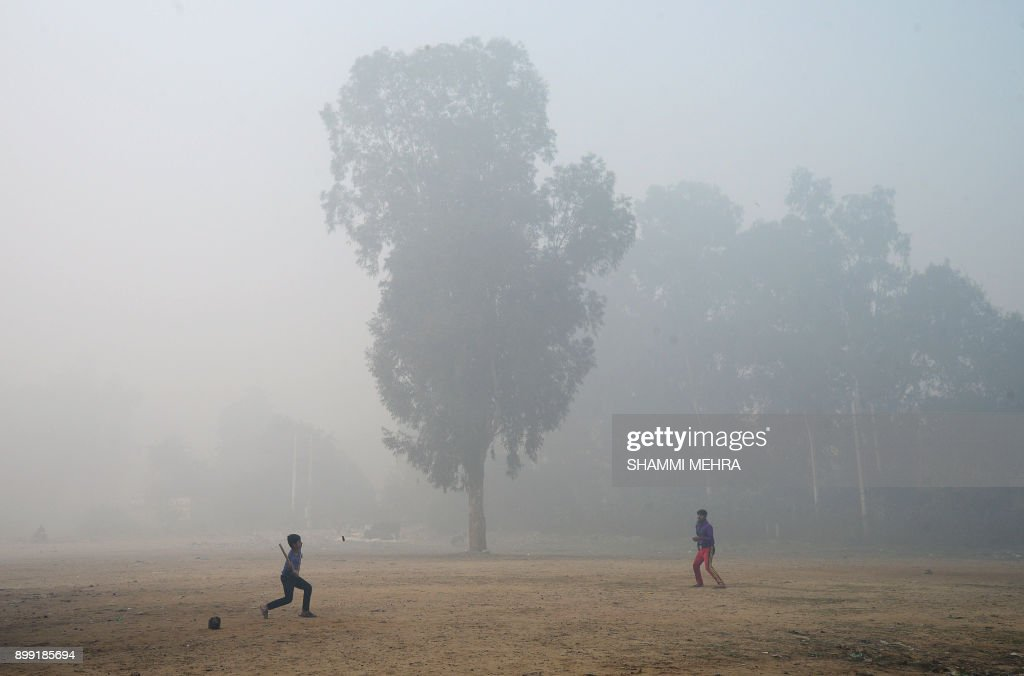 Indian children play a game in a field amid dense fog and air pollution in Jalandhar on December 28 2017 According to Indian environment authorities..