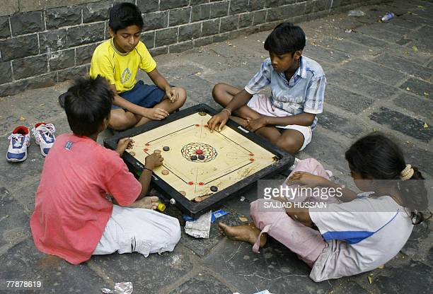 Indian children play a game of 'carrom' on the roadside in Mumbai 13 November 2007 Street children like these often have a tough childhood in India's...