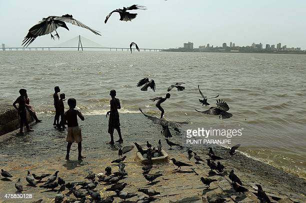 Indian children play at the seafront against the background of the BandraWorli Sea Link cablestayed bridge on a hot afternoon in Mumbai on June 4...