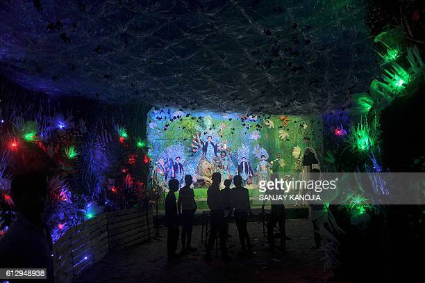 Indian children play inside a display with a marine life theme set up for the Dussehra festival in Allahabad on October 6 2016 Dussehra is a Hindu...