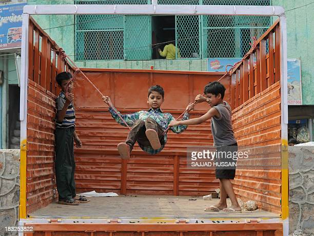 Indian children play on a swing strung up on the back of a truck in New Delhi on October 6 2013 Play is essential to optimal child development and...