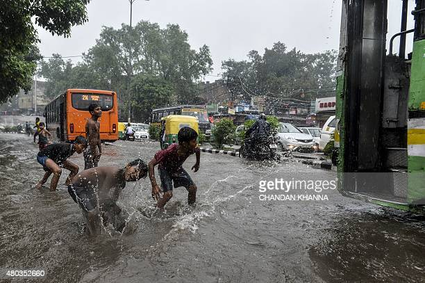Indian children play on the floodwaters on a street in New Delhi on July 11 as the Indian capital experienced heavy monsoon rainfall AFP PHOTO /...