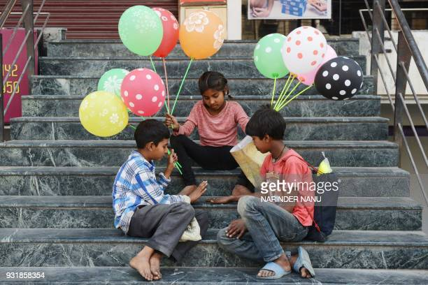 Indian children Playing with coin as they sells balloons in Amritsar on March 142018 / AFP PHOTO / NARINDER NANU