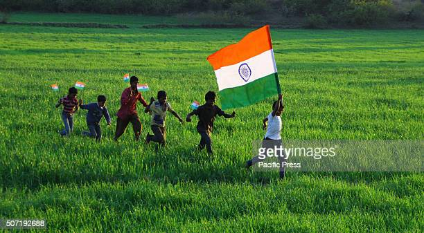 Indian children run with the national tricolor flags in the wheat farm and celebrate their Republic day