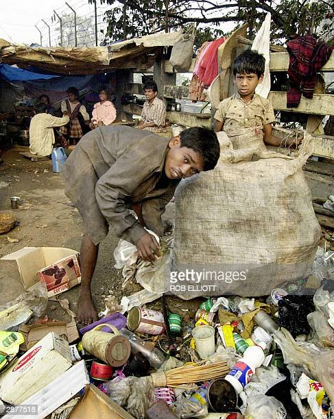 Indian children scavenge though rubbish for recyclable materials on the side of a bridge in Dharavi Bombay 17 January 2004 Poverty of this extreme is...