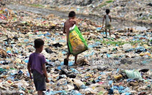 TOPSHOT Indian children searching for recyclable items walk through a garbage dump in Dimapur in the northeastern state of Nagaland on June 5 on...