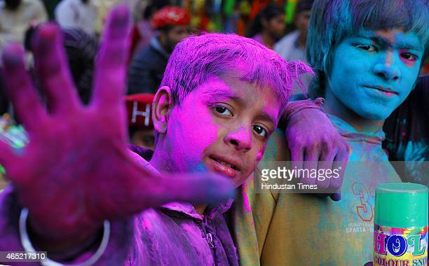 Indian children smeared with gulalcoloured powder smiles at the camera during Holi celebrations on March 4 2015 in New Delhi India Festival of colors...