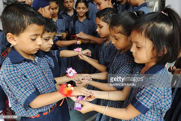Indian children tie 'rakhis' on each other's wrists on the eve of the Hindu festival Raksha Bandhan in a school in Amritsar August 4 2009 The annual...