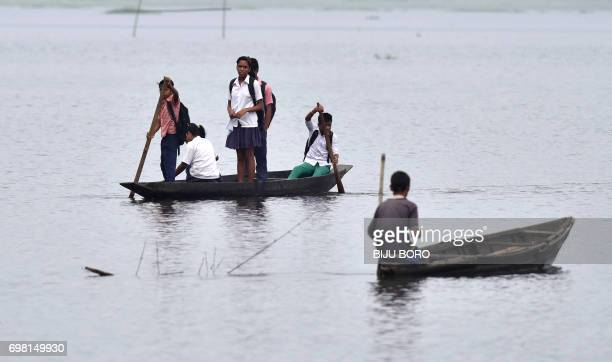Indian children travel to school on a boat across floodwaters in Rajbari village on the outskirts of Guwahati in Assam state on June 20 2017 / AFP...