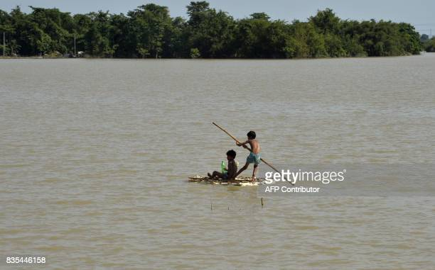Indian children uses a raft to travel over flood waters in Araria in Bihar state on August 19 2017 Nearly 600 people have died and millions have been...