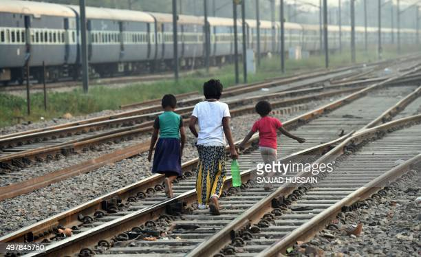 Indian children walk along the railway tracks after defecating in the open on International Toilet Day in New Delhi on November 19 2015 About 11...