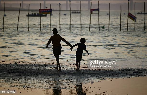 TOPSHOT Indian children walk on the bank of the Sangam the confluence of the three rivers Ganges Yamuna and mythical Saraswati in Allahabad on...