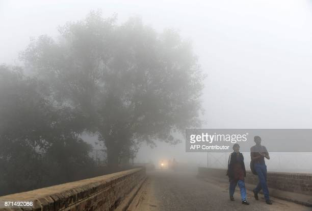 Indian children walk to their school amid heavy smog on the outskirts of New Delhi on November 8 2017 Delhi shut all primary schools on November 8 as...