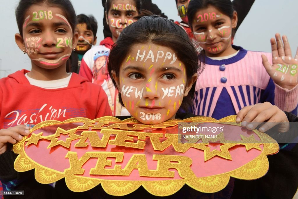 Indian children with their faces painted pose for a picture to welcome the New Year 2018 in Amritsar on December 31 2017 / AFP PHOTO / NARINDER NANU