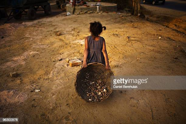 Indian children work nearby to their parents at a construction project in front of the Jawaharlal Nehru Stadium on January 30, 2010 in New Delhi,...
