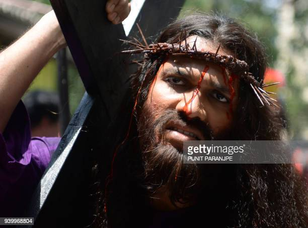 Indian Christian devotee Alan D'Souza portraying Jesus Christ carries a cross during a reenactment of the crucifixion in a Good Friday procession in...