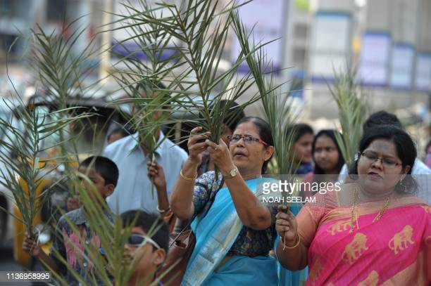 Indian Christian devotees carry palm branches during a Palm Sunday procession along a road in Secunderabad, the twin city of Hyderabad on April 14,...