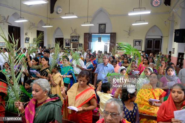 Indian Christian devotees hold palm branches during a Palm Sunday service at Wesley Church in Secunderabad the twin city of Hyderabad on April 14...