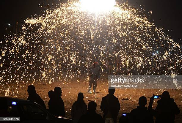 TOPSHOT Indian Christian devotees watch a fireworks display marking Christmas Eve outside St Peter's Church in Allahabad on December 24 2016 / AFP /...