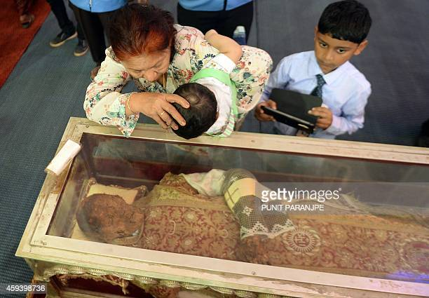 Indian Christian helps a child to kiss a casket carrying the remains of the St Francis Xavier at the Se Cathedral in Goa on November 22 2014 The 17th...