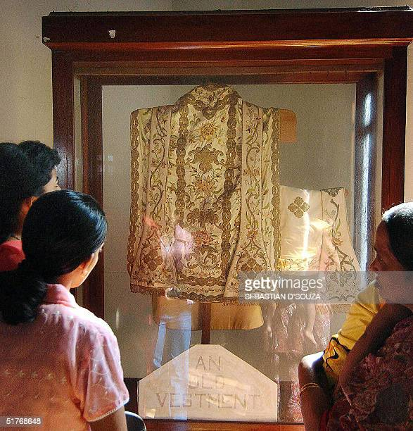 Indian Christian pligrims look at the vestments once worn by St Francis Xavier ahead of the exposition of his body at the Basilica of Bom Jesus in...