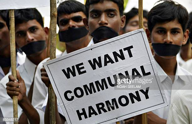 Indian Christians their mouths gagged with black cloth hold up a placard during a demonstration in Hyderabad on October 19 2008 The Catholic Bishops'...