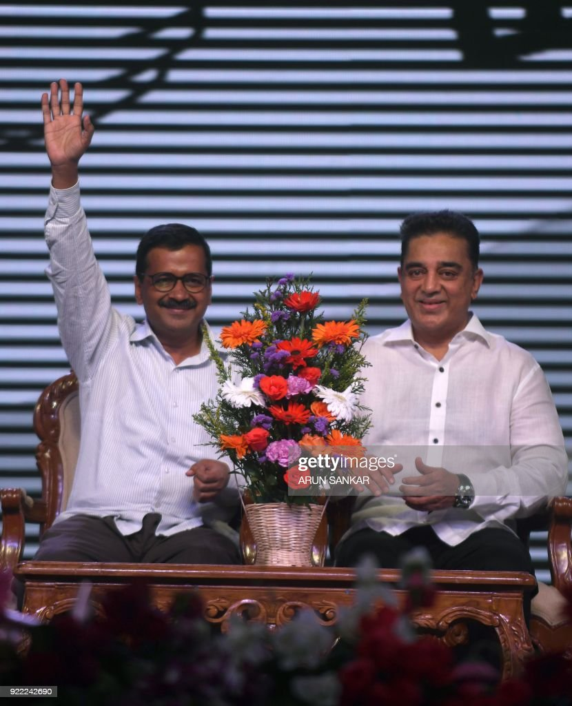 Indian cinema actor Kamal Hassan (R) sits next to the Chief Minister of Delhi Aravind Kejriwal during the launch of his new political party 'Makkal Needhi Mayyam' in Madurai on February 21, 2018. / AFP PHOTO / Arun SANKAR