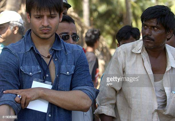 Indian cinema actor Vivek Oberoi is watched by an Indian tsunami victim fisherman as he brings a helping hand to tsunami relief efforts at a fishing...