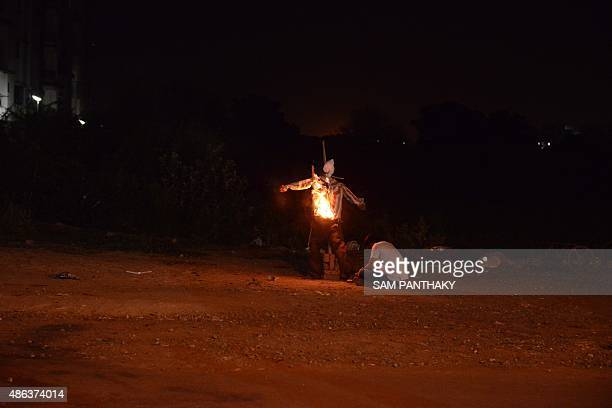 Indian citizen Kamleshbhai burns an effigy of the Convenor of the Patel Patidar Ananmat Andolan Hardik Patel in the New Ranip area on the outskirts...