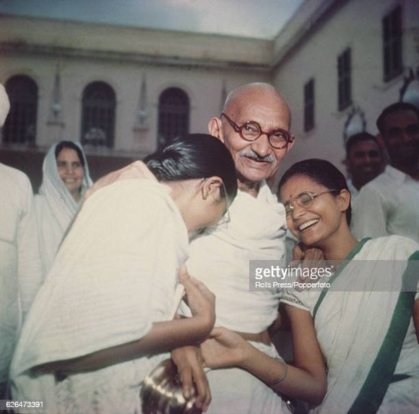 Indian civil rights and political leader Mahatma Gandhi pictured with two of his granddaughters at Binka House in New Delhi India circa 1947
