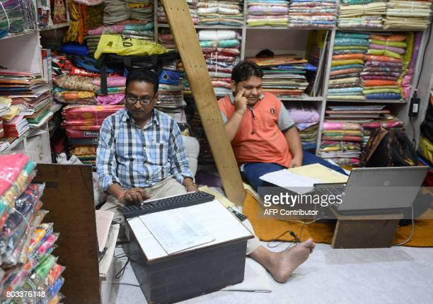 Indian cloth traders work at their shop in Allahabad on June 29 2017 India is bracing for upheaval as it storms ahead with its most ambitious reform...