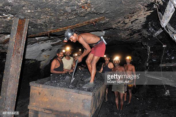 Indian coal miners load coal into transporting tubs inside an underground tunnel of a mine owned by the Sinagareni Collieries Company Limited at...