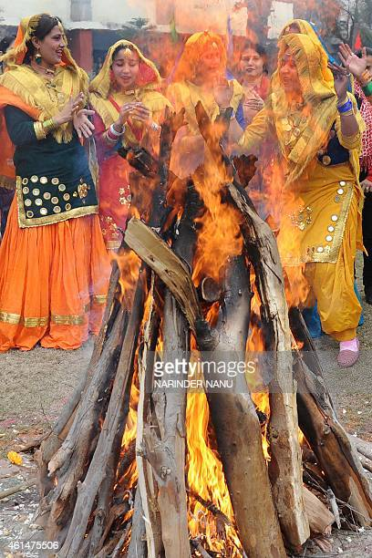 Indian college girls clad in traditional Punjabi dress perform the 'giddha' folk dance around a bonfire during celebrations of the Lohri festival in...