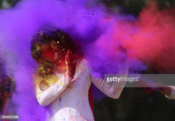 TOPSHOT Indian college girls throw coloured powder to one another during Holi festival celebrations in Bhopal on February 28 2018 Holi the popular...