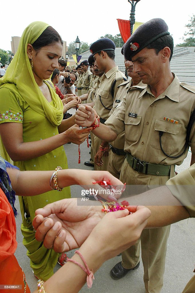 Indian college girls tie `rakhi` onto the wrists of Indian Border Security Force Jawans at the IndoPakistan border post at Wagah during the Hindu...
