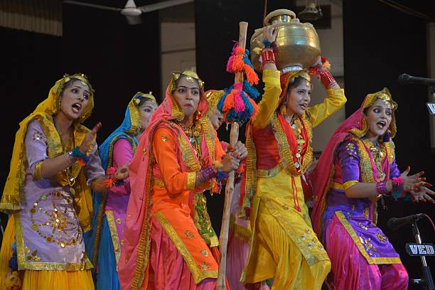 Indian college girls wear traditional Punjabi dress as they perform the Punjabi folk dance the `Giddha` during a competition at Guru Nanak Dev...