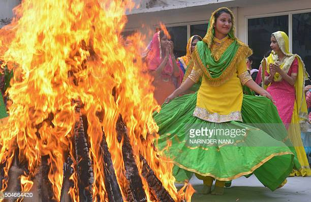 Indian college women clad in traditional Punjabi dress perform the 'giddha' folk dance around a bonfire during celebrations on the eve of the Lohri...