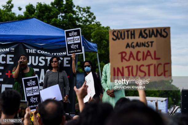 Indian community members show placards which reads Black Lives Matter as they protest at the makeshift memorial in honour of George Floyd on June 4...