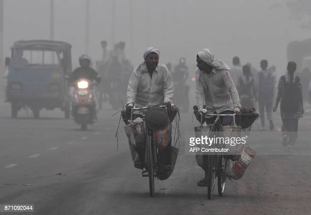 Indian commuters drive amid heavy smog in New Delhi on November 7 2017 New Delhi woke up to a choking blanket of smog on November 7 as air quality in...