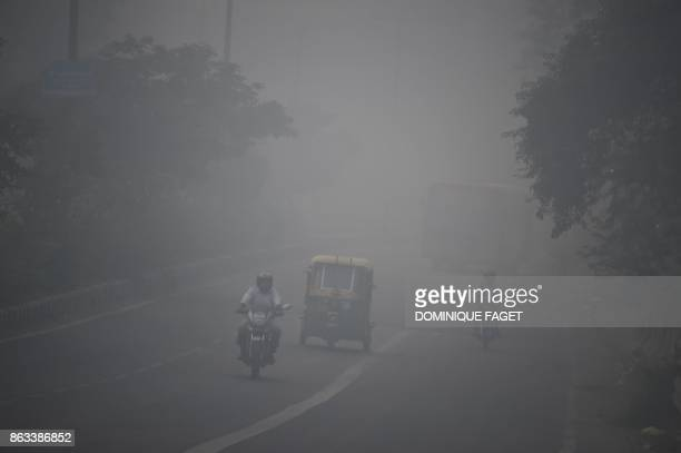 TOPSHOT Indian commuters drive amid heavy smog in New Delhi on October 20 the day after the Diwali Festival New Delhi was shrouded in a thick blanket...