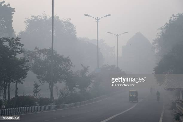 Indian commuters drive amid heavy smog in New Delhi on October 20 the day after the Diwali Festival New Delhi was shrouded in a thick blanket of...
