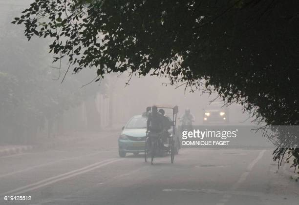 Indian commuters drive amid heavy smog in New Delhi on October 31 the day after the Diwali festival New Delhi was shrouded in a thick blanket of...