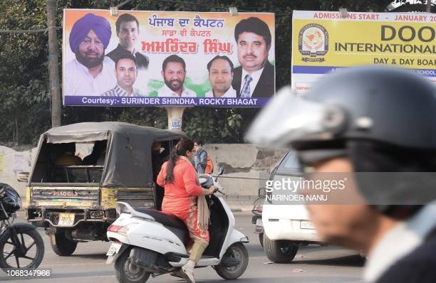 Indian commuters drive past a billboard with photographed Punjab chief minister Amarinder Singh along with Congress party chief Rahul Gandhi Punjab...