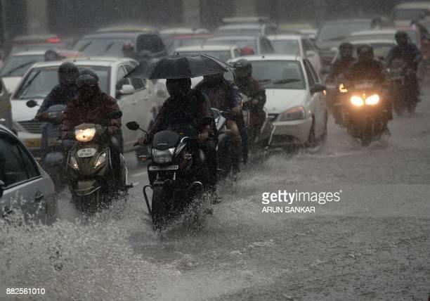 Indian commuters drive past during heavy monsoon rains in Chennai on November 30 2017 / AFP PHOTO / ARUN SANKAR