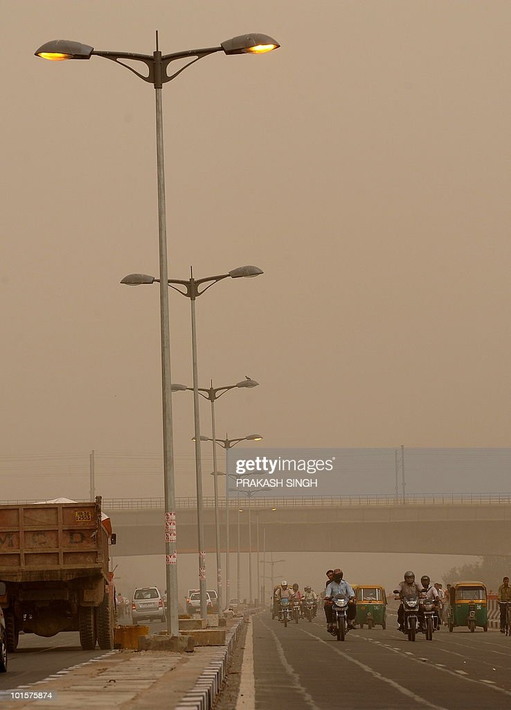 Indian commuters drive under a Delhi Metro overpass on a dusty morning in New Delhi on June 3, 2010. The dust storm is forecasted to be interspersed with light rain in some parts of the capital. AFP PHOTO/ Prakash SINGH